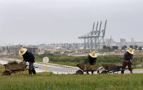 Landarbeiders in Cuba, met op de achtergrond freezone Mariel